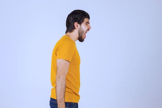 Mężczyzna W żółtej Koszuli Wygląda Na Przestraszonego I Podekscytowanego. Darmowe Zdjęcia