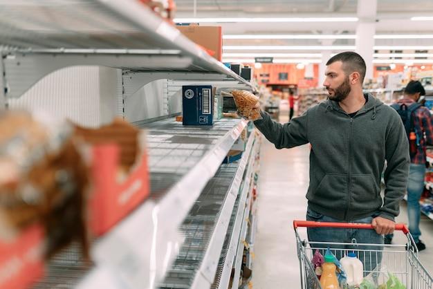 Mężczyzna Walczy O Zdobycie Podstawowych Artykułów Spożywczych W Supermarkecie, Takich Jak Spaguetti, Ryż I Inne Makarony Z Powodu Paniki Wywołanej Przez Koronawirusa (covid 19) Premium Zdjęcia