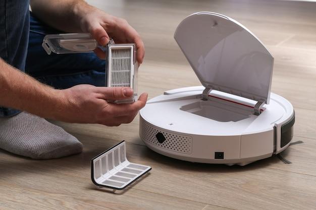 Mężczyzna Wkłada Filtr I Pojemnik, Aby Zbierać Kurz I Zanieczyszczenia Do Robota Odkurzającego Premium Zdjęcia