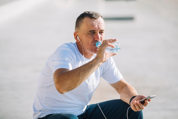Mężczyzna woda pitna z hełmofonami w jego ucho Darmowe Zdjęcia