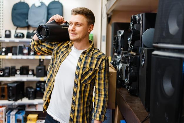 Mężczyzna Wybiera System Muzyczny W Sklepie Elektronicznym. Mężczyzna Kupuje Domowe Urządzenia Elektryczne Na Rynku Premium Zdjęcia