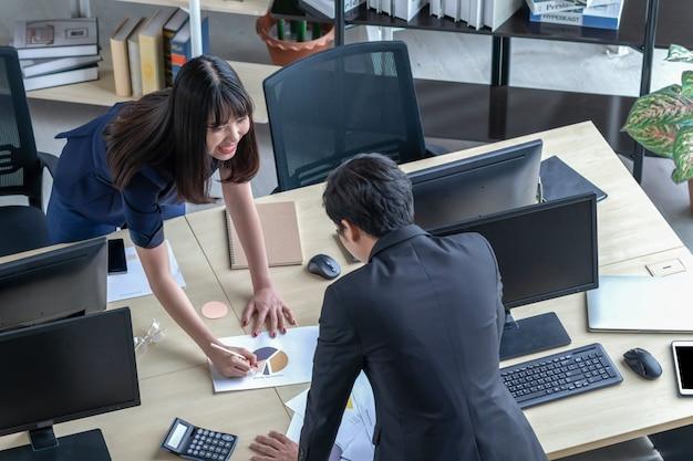 Mężczyzna wyjaśnia pracę dziewczynie przy biurku. Premium Zdjęcia