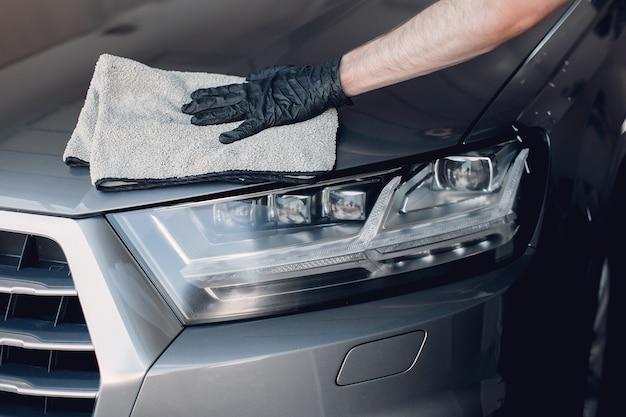 Mężczyzna wypolerować samochód w garażu Darmowe Zdjęcia