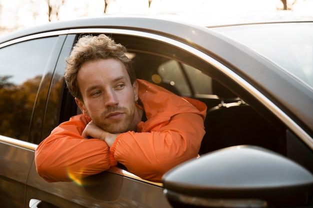 Mężczyzna Wystawiający Głowę Przez Okno Samochodu Podczas Podróży Darmowe Zdjęcia