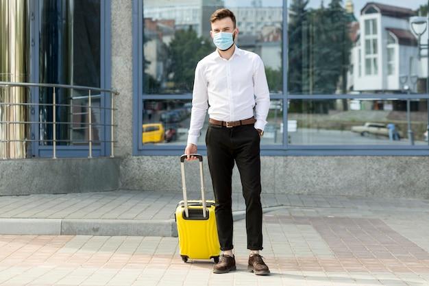 Mężczyzna Z Bagażem Na Sobie Maskę Premium Zdjęcia