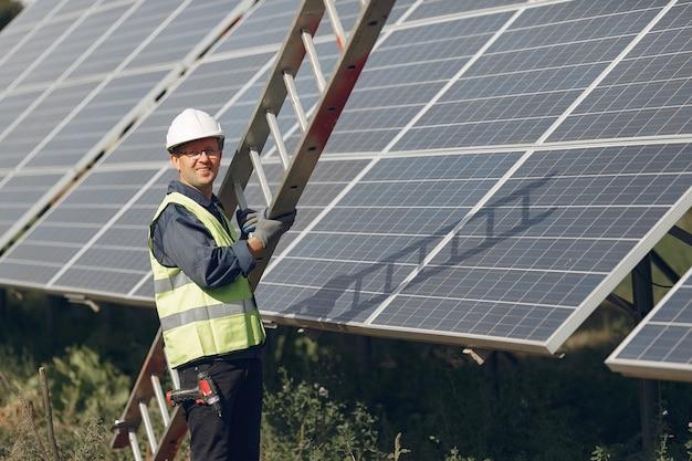 Mężczyzna Z Białym Hełmem Blisko Panelu Słonecznego Darmowe Zdjęcia
