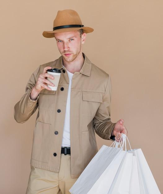 Mężczyzna z białymi torba na zakupy i kawą Darmowe Zdjęcia