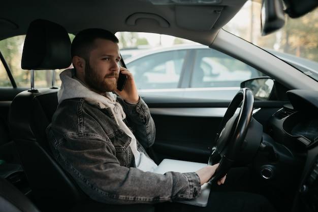 Mężczyzna Z Brodą W Przypadkowych Ubraniach Robi Interesy Na Smartfonie W Samochodzie, Na Kolanach Leży Laptop. Facet Zatrzymał Samochód, Aby Natychmiast Zdalnie Rozwiązać Zadania W Pracy W Dystansie Społecznym Premium Zdjęcia