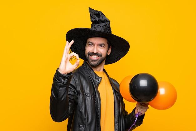 Mężczyzna Z Czarownica Kapeluszem Trzyma Czarnych I Pomarańczowych Lotniczych Balony Dla Halloween Przyjęcia Pokazuje Ok Znaka Z Palcami Premium Zdjęcia