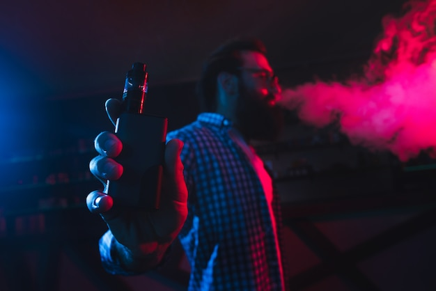 Mężczyzna Z Elektronicznym Papierosem W Ręku Wytwarza Dym Premium Zdjęcia
