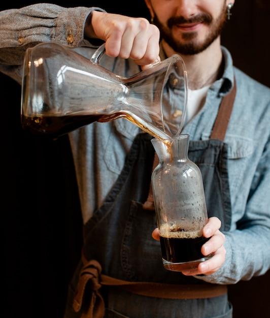 Mężczyzna z fartuchem nalewa kawę w słoju Darmowe Zdjęcia