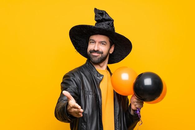 Mężczyzna Z Kapeluszem Wiedźmy, Trzymając Czarne I Pomarańczowe Balony Na Halloween Party, Drżenie Rąk Do Zamknięcia Dobrą Ofertę Premium Zdjęcia