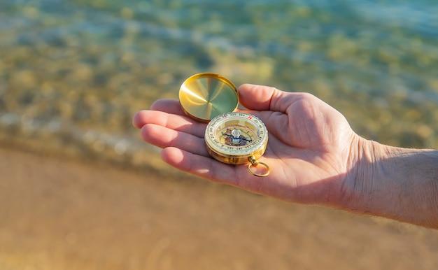 Mężczyzna Z Kompasem W Rękach Blisko Morza. Selektywne Ustawianie Ostrości. Premium Zdjęcia
