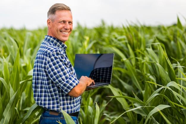 Mężczyzna z laptopem patrzeje kamerę Darmowe Zdjęcia