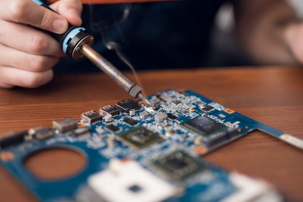 Mężczyzna Z Lutownicą Naprawia Sprzęt Komputerowy. Premium Zdjęcia