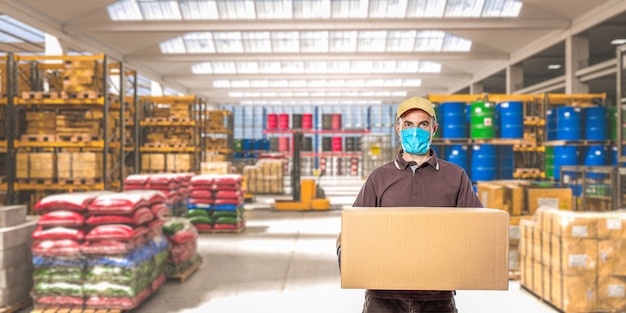 Mężczyzna Z Maską I Paczką, Wnętrze Magazynu Przemysłowego, W Którym Przechowywane Są Różne Towary. Premium Zdjęcia