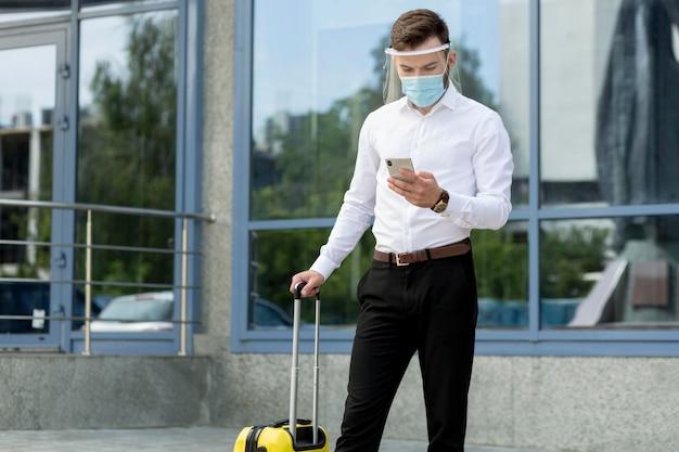 Mężczyzna Z Maską I Sprawdzaniem Bagażu Telefonu Darmowe Zdjęcia