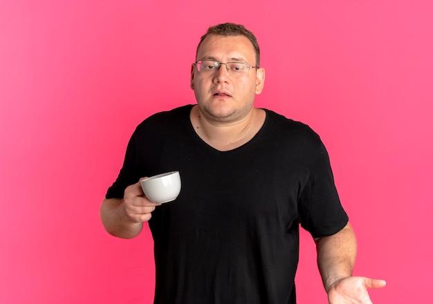 Mężczyzna Z Nadwagą W Okularach Na Sobie Czarną Koszulkę Trzymający Filiżankę Kawy Wzruszający Ramionami, Patrząc Zdezorientowany Stojąc Nad Różową ścianą Darmowe Zdjęcia