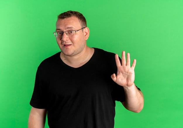 Mężczyzna Z Nadwagą W Okularach Na Sobie Czarną Koszulkę Wygląda Zdziwiony Macha Ręką Stojącą Na Zielonej ścianie Darmowe Zdjęcia