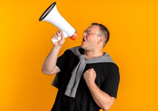 Mężczyzna Z Nadwagą W Okularach, Ubrany W Czarną Koszulkę, Krzyczy Do Megafonu, Zaciskając Pięść Stojącą Nad Pomarańczową ścianą Darmowe Zdjęcia