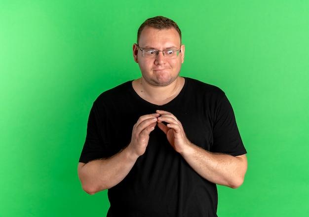 Mężczyzna Z Nadwagą W Okularach, Ubrany W Czarną Koszulkę, Patrząc Na Bok Przebiegle Trzymający Dłonie Razem, Stojący Nad Zieloną ścianą Darmowe Zdjęcia