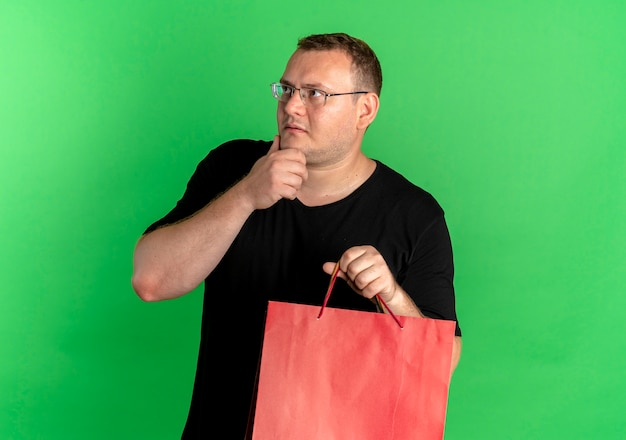 Mężczyzna Z Nadwagą W Okularach, Ubrany W Czarną Koszulkę, Trzymający Papierowe Torby, Patrząc Zdziwiony, Stojąc Nad Zieloną ścianą Darmowe Zdjęcia