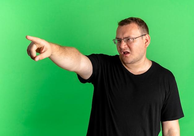 Mężczyzna Z Nadwagą W Okularach Ubrany W Czarną Koszulkę Wyglądający Na Niezadowolonego, Wskazujący Na Komet Z Palcem Wskazującym Stojącym Nad Zieloną ścianą Darmowe Zdjęcia