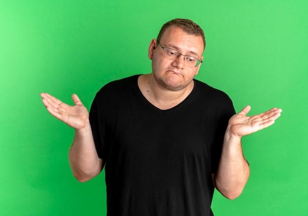 Mężczyzna Z Nadwagą W Okularach, Ubrany W Czarną Koszulkę, Wyglądający Na Zdezorientowanego I Niepewnego, Rozłożony Na Boki, Bez Odpowiedzi, Stojący Nad Zieloną ścianą Darmowe Zdjęcia
