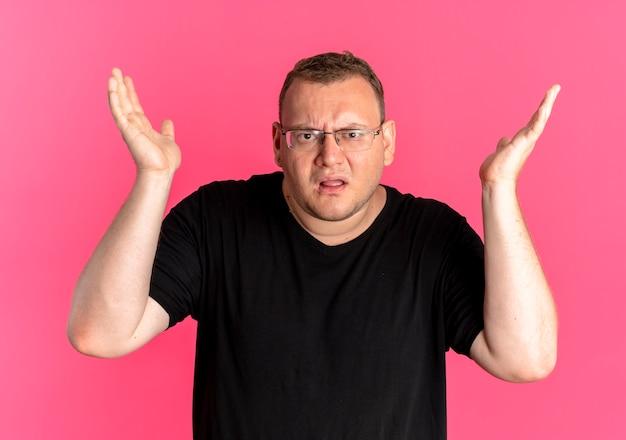 Mężczyzna Z Nadwagą W Okularach, Ubrany W Czarną Koszulkę, Zdezorientowany I Niezadowolony Z Podniesionymi Rękami, Pytając Lub Kłócąc Się, Stojąc Nad Różową ścianą Darmowe Zdjęcia