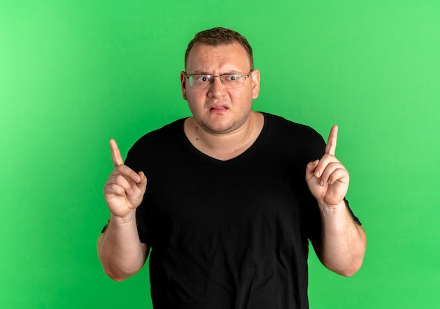 Mężczyzna Z Nadwagą W Okularach, Ubrany W Czarny T-wygląd, Zdezorientowany, Wskazujący Palcami W Górę Nad Zieloną ścianą Darmowe Zdjęcia