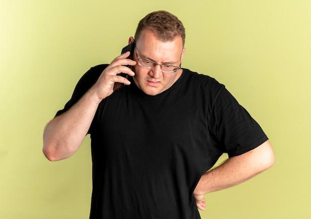 Mężczyzna Z Nadwagą W Okularach W Czarnej Koszulce Wyglądający Na Zdezorientowanego I Niezadowolonego Podczas Rozmowy Przez Telefon Komórkowy Stojący Nad Jasną ścianą Darmowe Zdjęcia