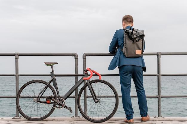 Mężczyzna Z Plecakiem Stojący Obok Swojego Roweru Darmowe Zdjęcia