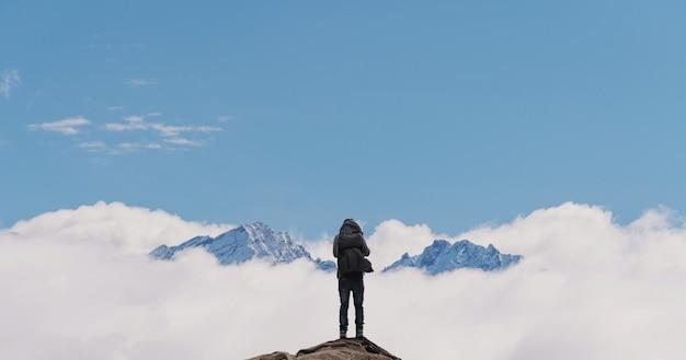 Mężczyzna Z Plecakiem Stojący Samotnie Na Szczycie Góry Premium Zdjęcia