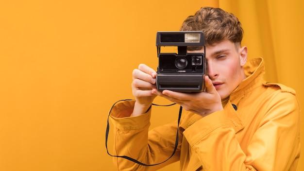 Mężczyzna z retro kamerą w żółtej scenie Darmowe Zdjęcia