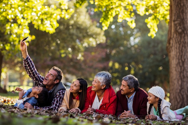 Mężczyzna Z Rodziną Bierze Selfie Przy Parkiem Premium Zdjęcia