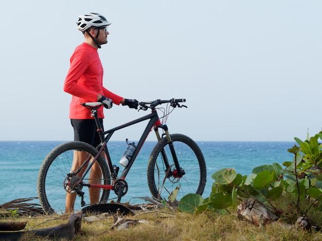 Mężczyzna Z Rowerem Stoi Na Brzegu Oceanu Premium Zdjęcia