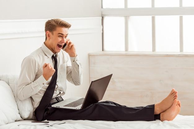 Mężczyzna z telefonem komórkowym i używać laptopem podczas gdy siedzący na łóżku Premium Zdjęcia