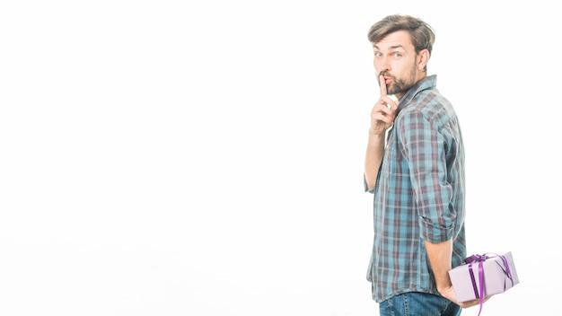 Mężczyzna z valentine prezentem robi cisza gestowi na białym tle Darmowe Zdjęcia