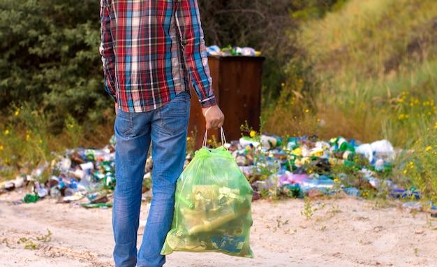 Mężczyzna Z Workiem Na śmieci Czyści Obszar śmieci Premium Zdjęcia