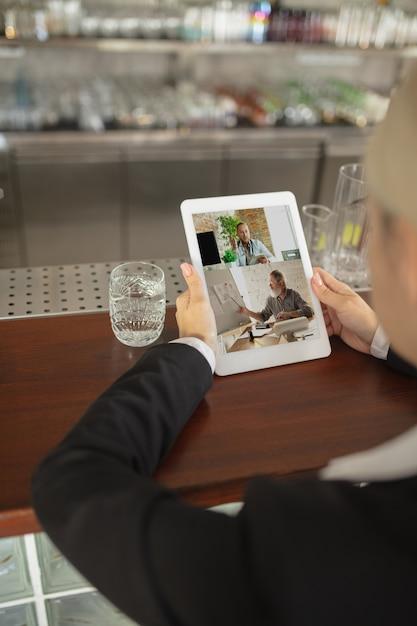 Mężczyzna Za Pomocą Tabletu Do Wideokonferencji Podczas Picia Wody Darmowe Zdjęcia