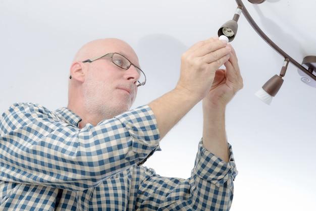 Mężczyzna Zamienia żarówkę W Domu Premium Zdjęcia