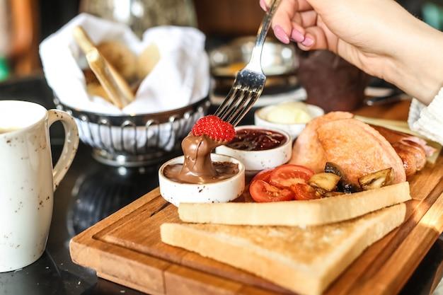 Mężczyzna Zanurza Truskawkę W Czekoladowym Maśle Zestaw śniadaniowy Toast Pomidorowy Miód Widok Z Boku Darmowe Zdjęcia