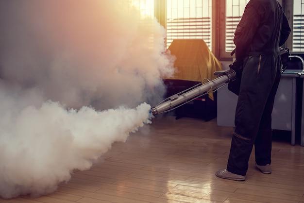 Mężczyzna Zaparowuje, Aby Wyeliminować Komara, Aby Zapobiec Rozprzestrzenianiu Się Gorączki Denga I Wirusa Zika Premium Zdjęcia
