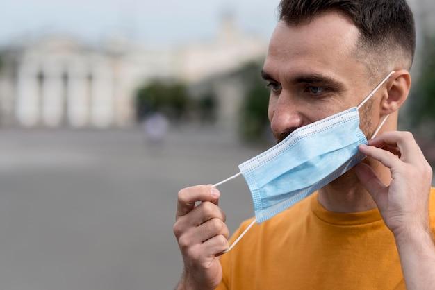 Mężczyzna Zdejmując Maskę Medyczną Na Zewnątrz Darmowe Zdjęcia