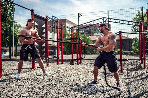 Mężczyźni ciężko pracują z liną na podwórku siłowni. trening na świeżym powietrzu. fitness, sport, ćwiczenia, trening i styl życia. Premium Zdjęcia