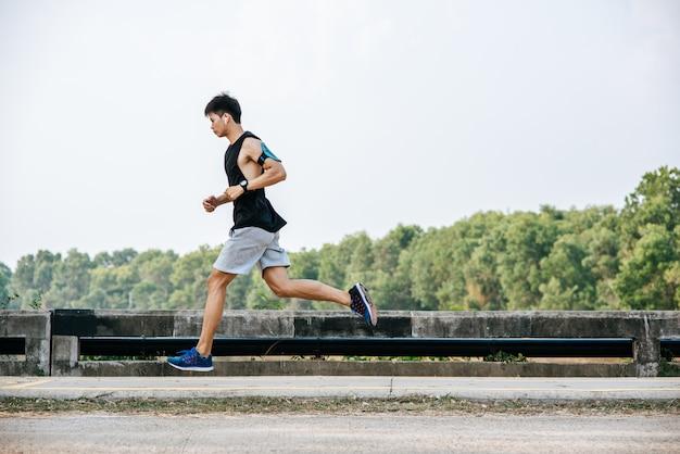 Mężczyźni ćwiczą Biegając Po Drodze Po Moście. Darmowe Zdjęcia