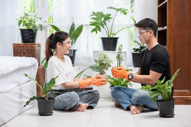 Mężczyźni I Kobiety W Pomarańczowych Rękawiczkach Siedzieli I Sadzili Drzewa W Domu. Darmowe Zdjęcia