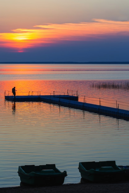 Mężczyźni Na Molo Pontonowym O Zachodzie Słońca Premium Zdjęcia