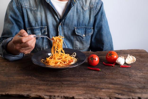 Mężczyźni noszą koszule jego gospodarstwa spaghetti z łyżką umieszczony na drewnianym stole Premium Zdjęcia