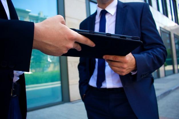 Mężczyźni przekazują się sobie w rękach książki elektronicznej Premium Zdjęcia